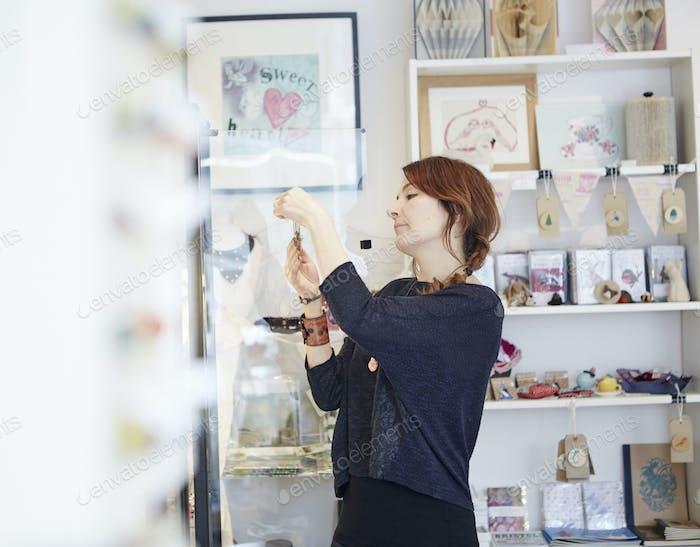 Una mujer madura en una tienda de regalos y joyas, mirando de cerca un objeto.