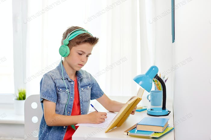 student boy in headphones writing to notebook
