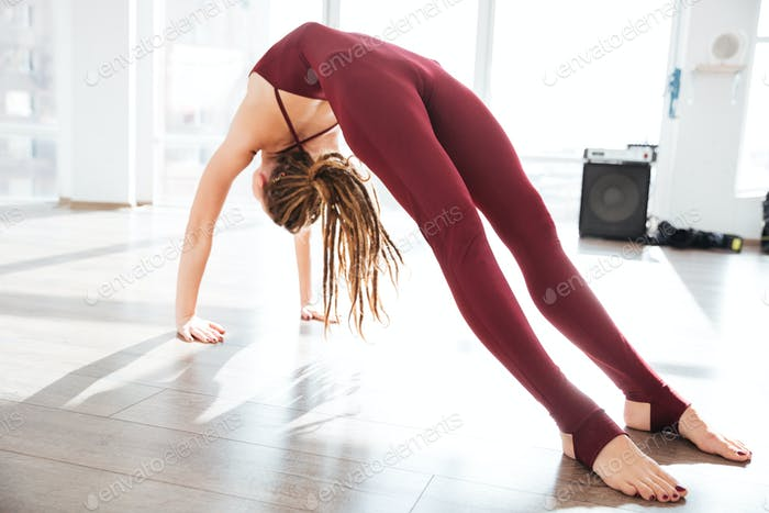 Attractive young woman bending and stretching in yoga studio