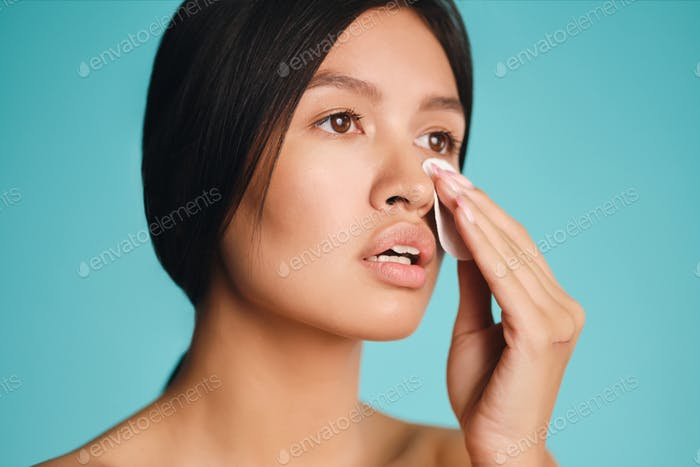 Portrait of beautiful Asian brunette girl cleaning face with sponge over colorful background
