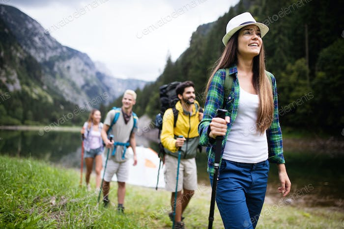 Group of smiling friends hiking with backpacks outdoors. Travel, tourism, hike and people concept