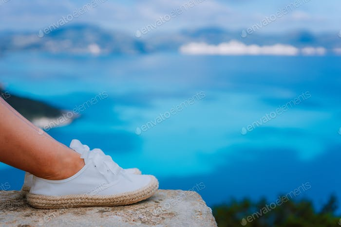 Woman feet wearing white espadrilles in front of beautiful seascape. Funny and happy fashion young