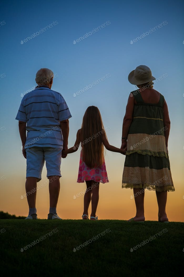 Girl with grandparents, sunset sky