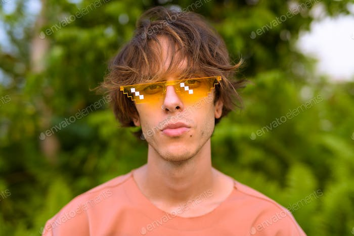 Young handsome rebellious man outdoors wearing glasses