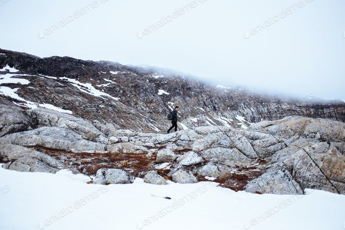 Distant image of male hiker walking on mountain landscape
