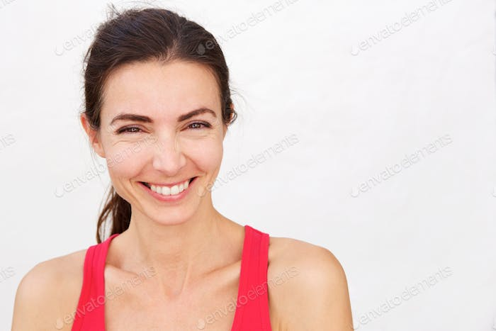 Close up cheerful young sports woman smiling over white background