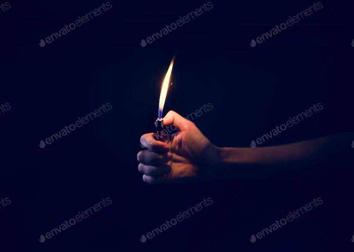 Hand holding lit lighter in the dark