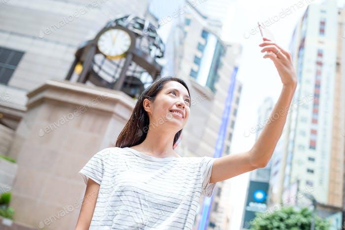 Woman taking selfie in causeway bay of Hong Kong city