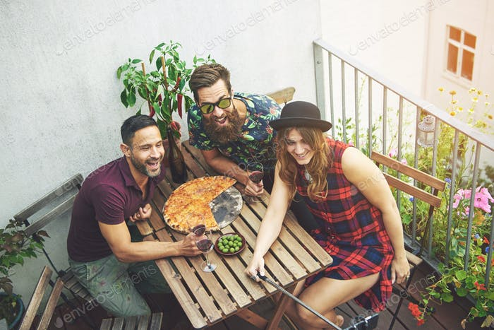 Woman in checkered dress takes photo with friends
