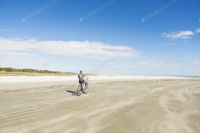 A teenage girl cycling on a beach