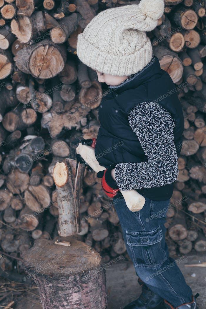 Kleiner Junge hackt Brennholz im Vorgarten zur Tageszeit.