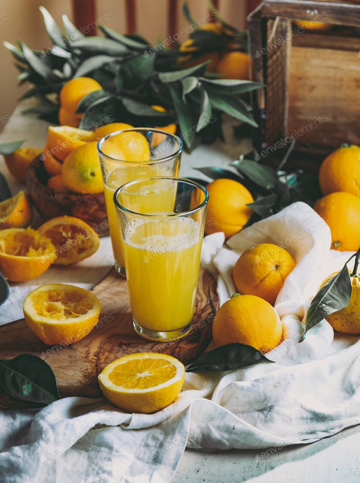 Orange Erntekonzept. Tisch mit Orangensaft und Schachtel mit Orangen und Orangenblättern.