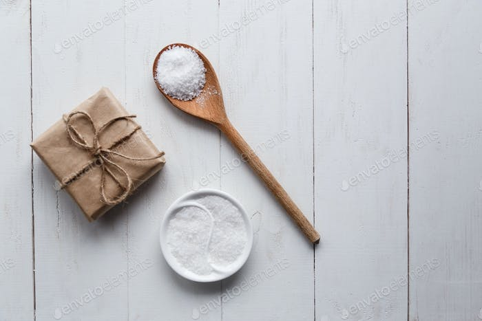 Healthy Sea Salt with giftbox on white wooden background. Flat lay. Copy space.