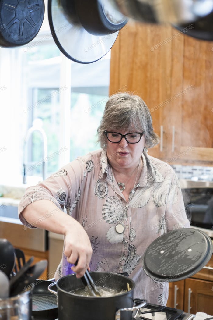 Senior woman checking to see if a pot of pasta is cooking correctly in a home kitchen.