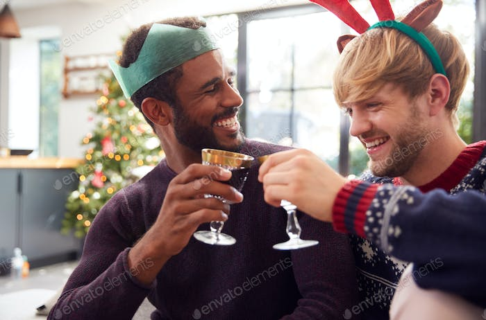 Gay Male Couple At Home In Fancy Dress Antlers And Paper Hat Making A Toast On Christmas Day