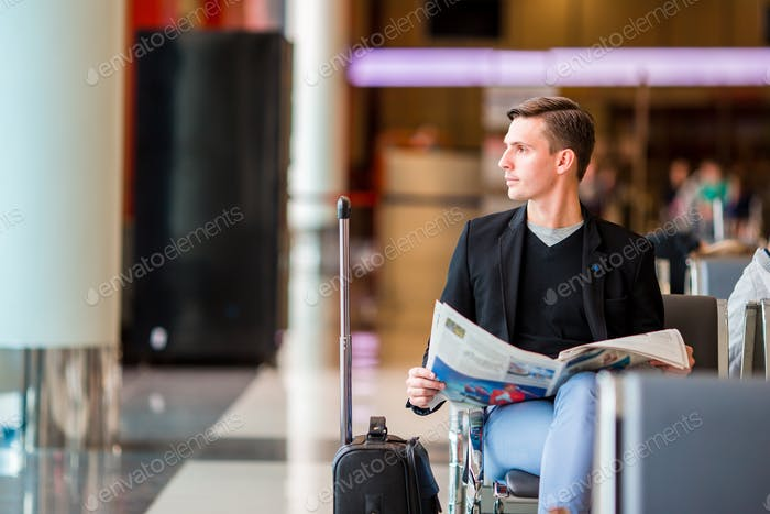 Young caucasian man with newspaper at the airport while waiting for boarding. Casual young