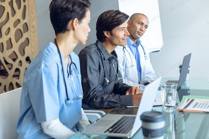 Diverse medical team with stethoscopes around the neck discussing at the table in hospital