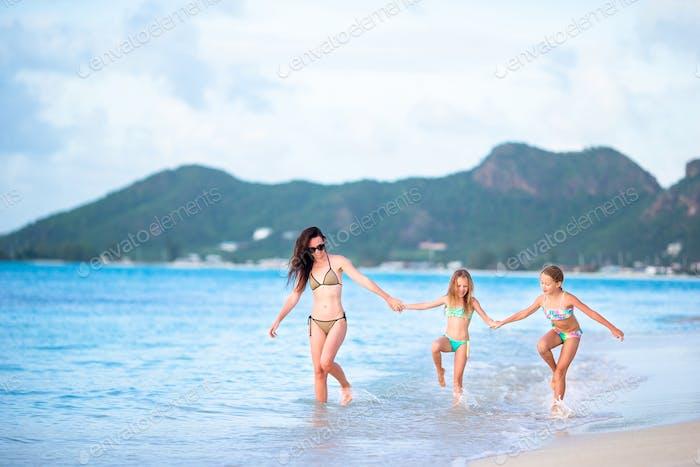 schön Mutter und ihr entzückend kleine Töchter auf die Strand