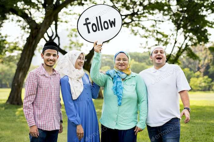 Muslim family holding up a follow sign