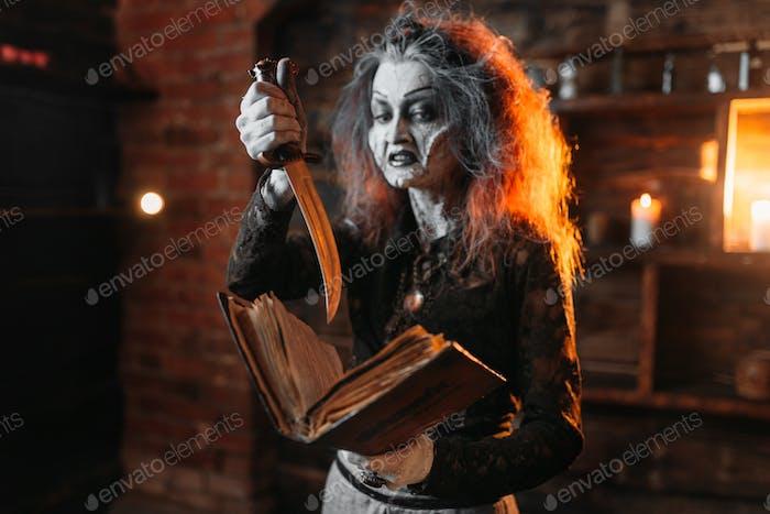 Gruselige Hexe hält Zauberbuch und Messer