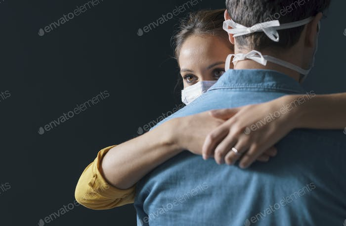 Millennials couple wearing a protective face mask and hugging