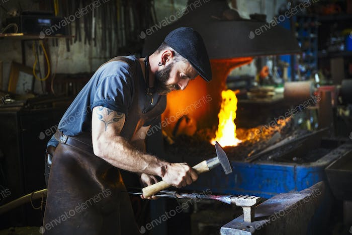 A blacksmith uses complex tools to hammer a cone of red hot metal on an anivil in a workshop.