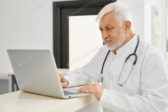 Eldery doctor in coat using laptop on reception