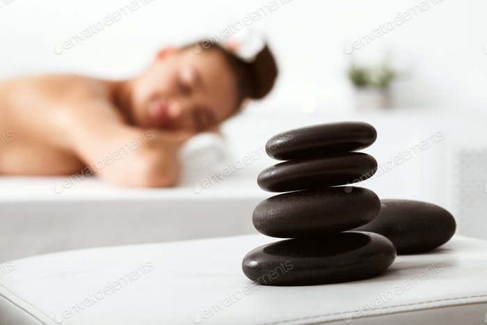 Stones for massage on foreground, woman relaxing with closed eyes