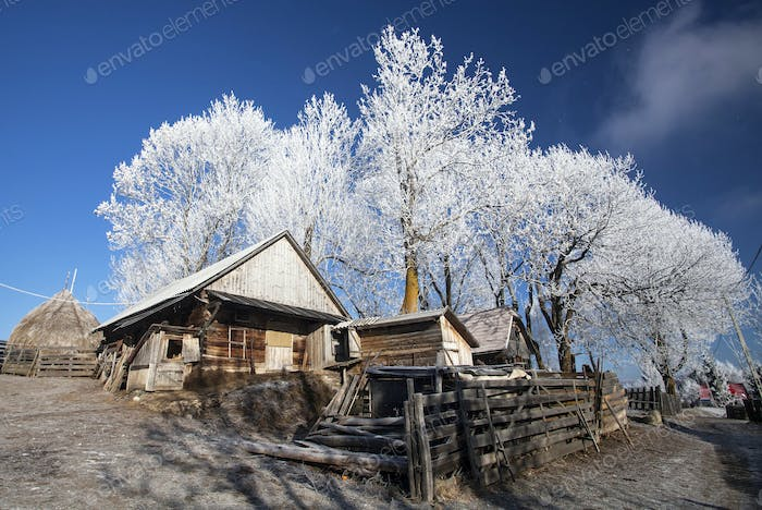 Winter rural landscape with cottage on the hill