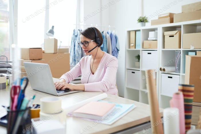Contemporary online shop manager in headset chatting with clients