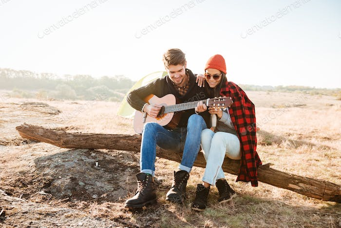 Couple having fun outdoors with guitar while sitting at campsite