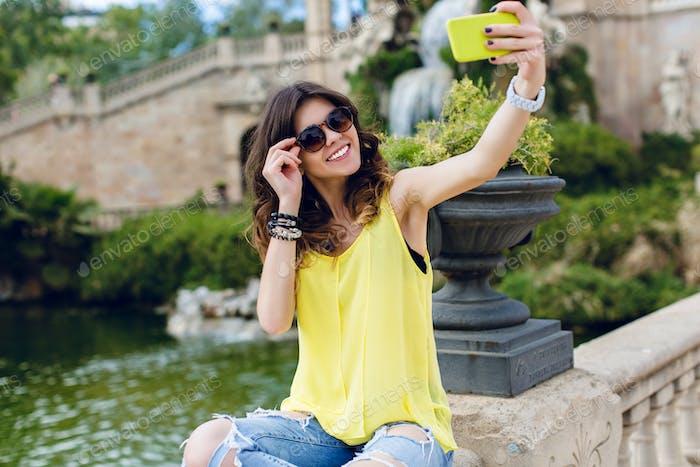 Cute brunette girl is making selfie-portrait on fence near sea on sightseeing background. She wears