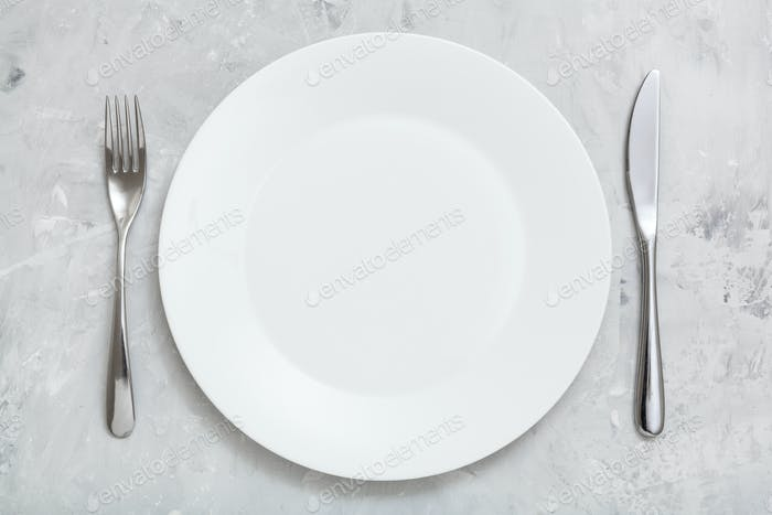 top view white plate with knife, spoon on concrete