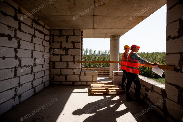 Two young civil engineers dressed in orange work vests and helmet stand on the building site inside