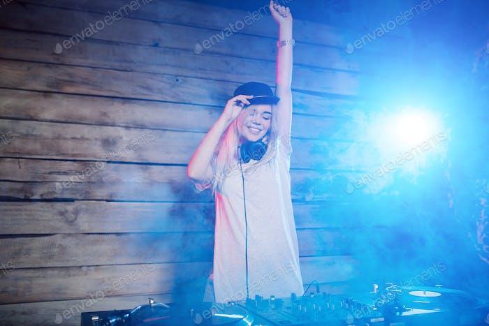 Cute dj woman having fun playing music at club party