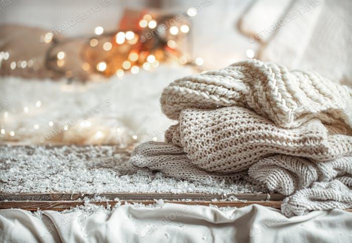 Winterhintergrund mit gestrickten Elementen auf unscharfem Hintergrund.