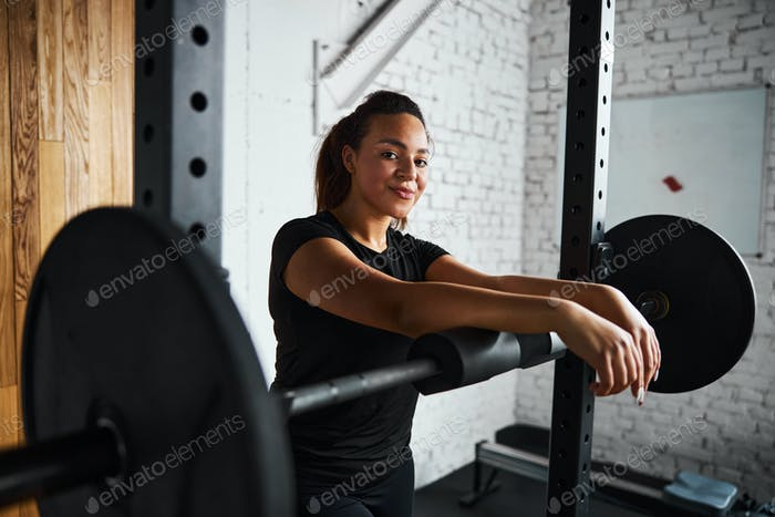 Smiling young woman exercising with barbell indoors
