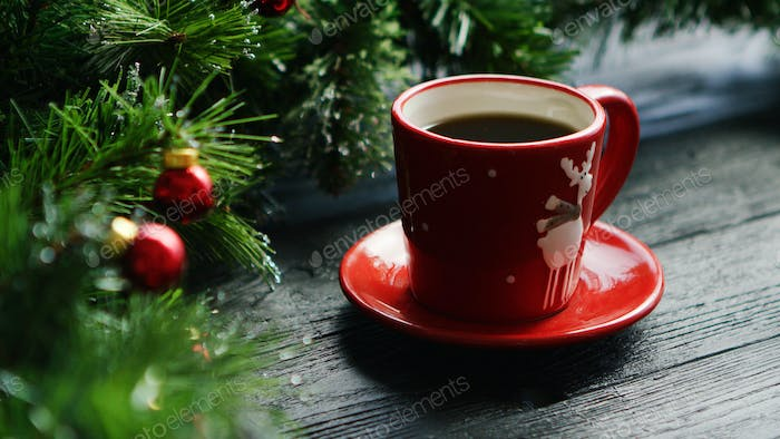 Hot beverage near decorated conifer branches