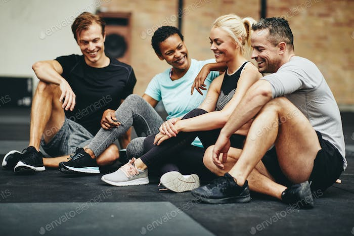 Smiling friends sitting in a gym talking together after exercising