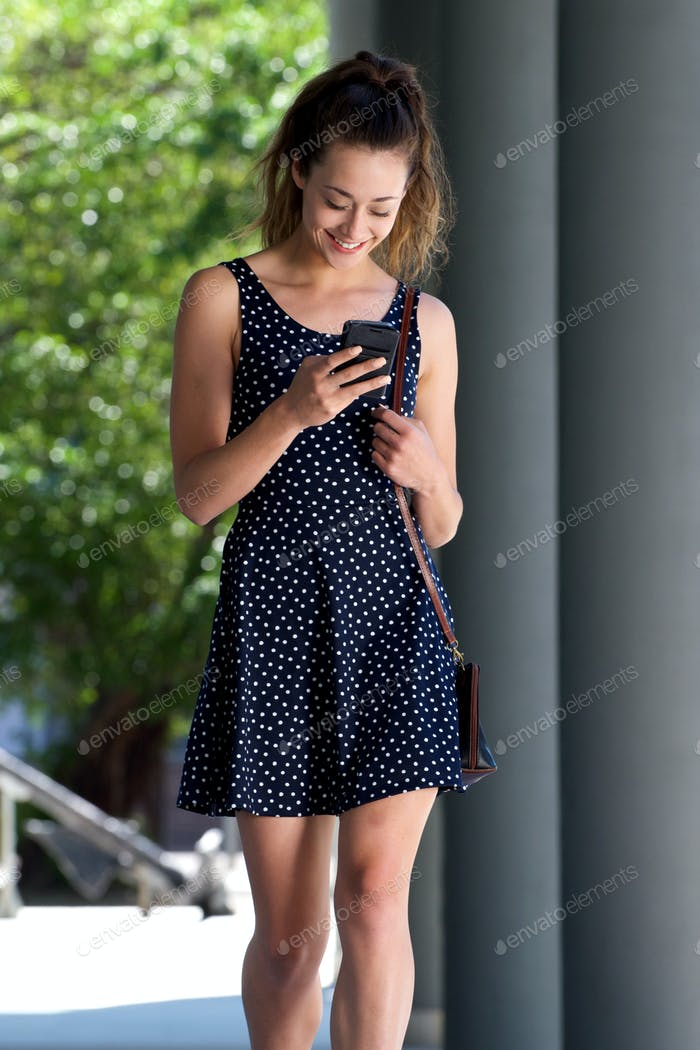 happy young woman in dress using mobile phone outside
