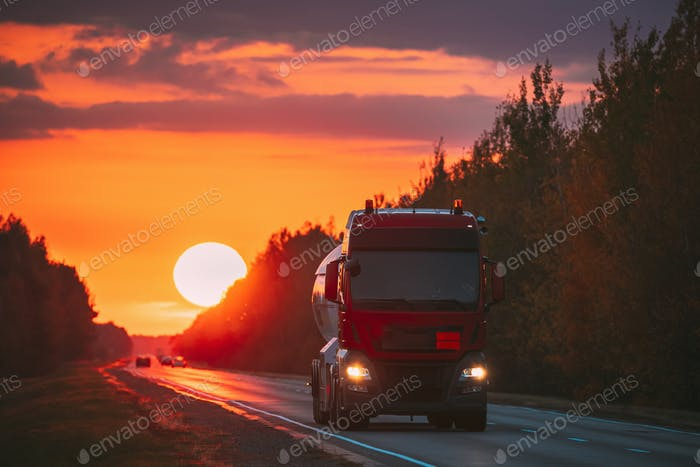 Red Truck Or Tractor Unit, Prime Mover, Traction Unit In Motion On Road, Freeway. Asphalt Motorway
