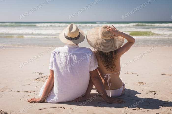 Young Caucasian couple relaxing sittingface to the sea at beach on a sunny day.