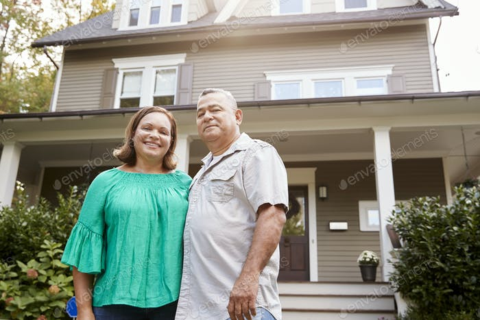 Portrait Of Smiling Senior Couple In Front Of Their Home