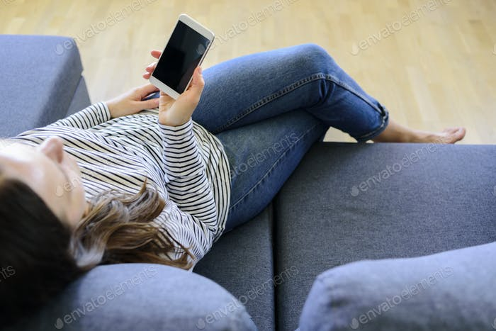 Woman using mobile phone on couch