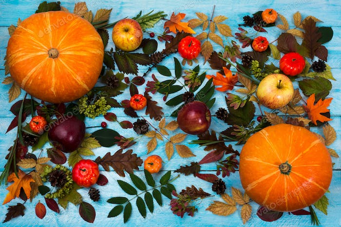 Thanksgiving greeting with fall leaves and pumpkin on blue backg