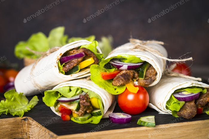 Burritos tortilla wraps with beef and vegetables on wooden close