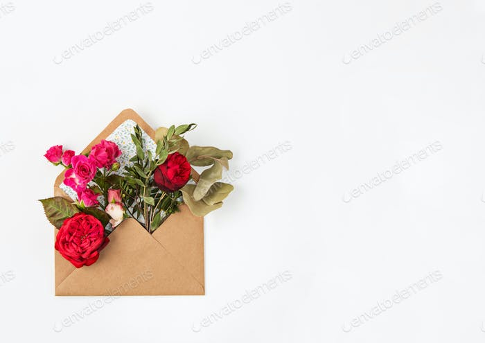 Love or valentine's day concept. Red beautiful roses in envelopen