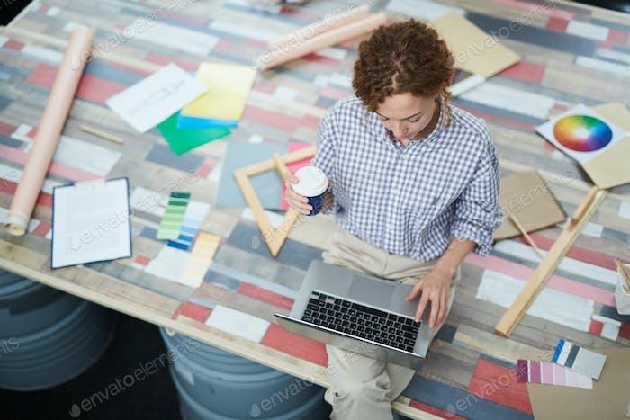 Serious lady designer using laptop in creative studio