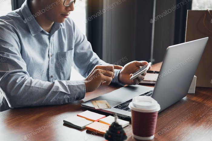Hands of man are holding smart phones and using laptops