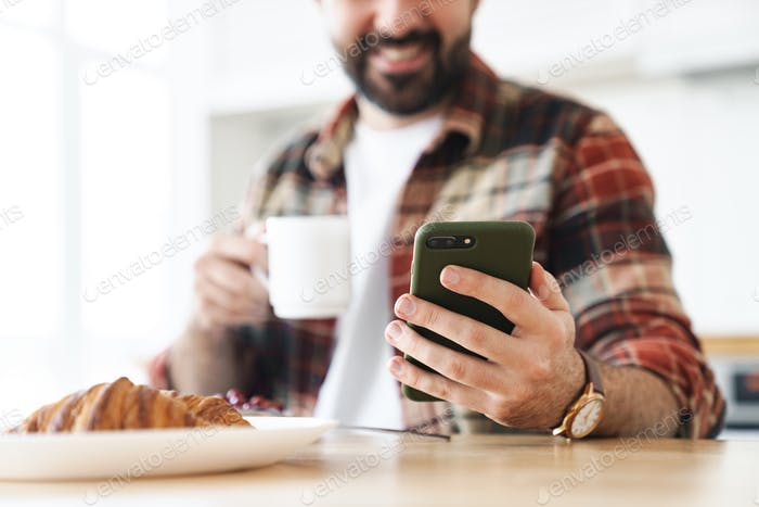 Retrato recortado del hombre alegre usando el teléfono celular y bebiendo café